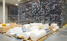 O armazém não só acomoda dezenas de milhares de tecidos, como também deve ser capaz de localizar com rapidez um rolo específico