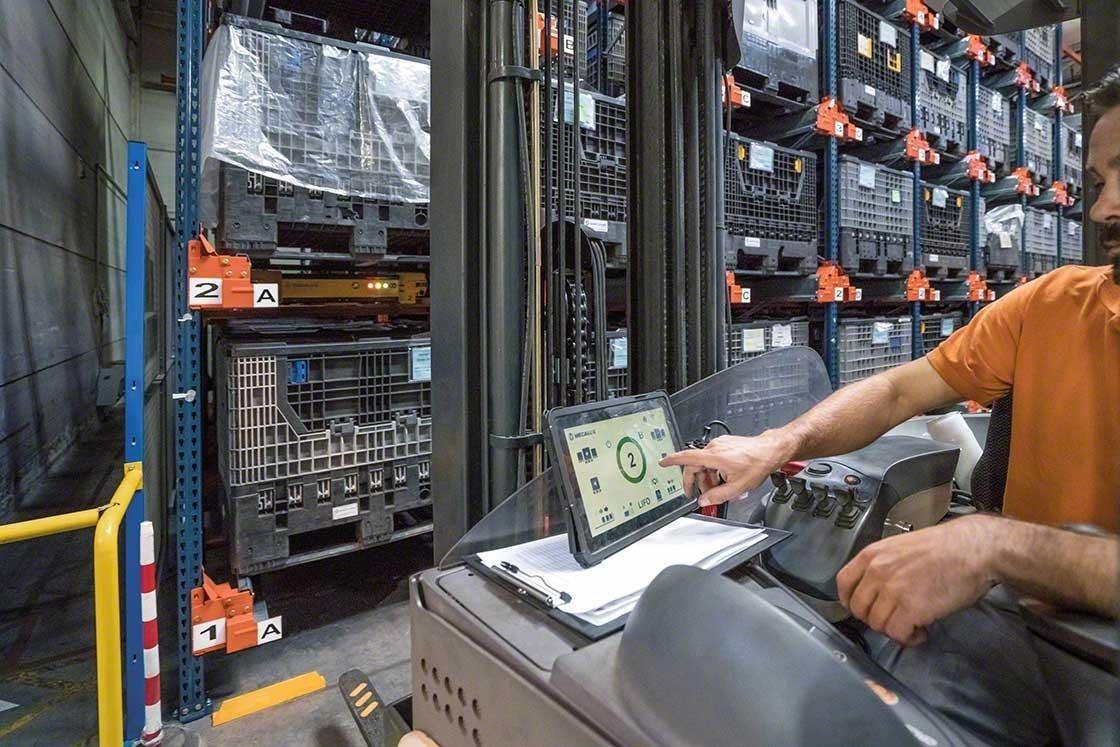 Um operador manuseia o Pallet Shuttle a partir da empilhadeira com um tablet digital em um armazém robotizado